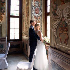 Brautpaar steht am hohen Fenster im Trauzimmer mit bunter Wandmalerei und braunen Fensterrahmen - Frühlingszimmer Herrenhäuser Gärten Hannover © Hochzeitsfotograf www.hochzeitsverliebt.de