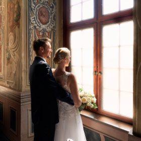 Das Brautpaar steht kuschelnd am Fenster und schaut in den hellen Tag hinaus - Frühlingszimmer Herrenhäuser Gärten Hannover © Hochzeitsfotograf www.hochzeitsverliebt.de