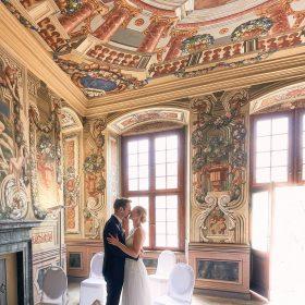 Ein Brautpaar steht im Trauraum mit bunt bemalter Wandmalerei und küsst sich - Frühlingszimmer Herrenhäuser Gärten Hannover © Hochzeitsfotograf www.hochzeitsverliebt.de