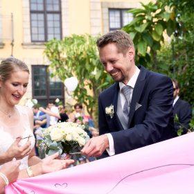 Brautpaar im Freien schneidet mit Nagelschere ein pinkes Tuch durch - Herrenhäuser Gärten Hannover © Hochzeitsfotograf www.hochzeitsverliebt.de