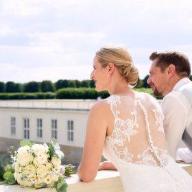 Das Brautpaar beugt sich leicht über den Balkon und schaut in die Ferne des Großen Garten - Herrenhäuser Gärten Hannover © Hochzeitsfotograf www.hochzeitsverliebt.de