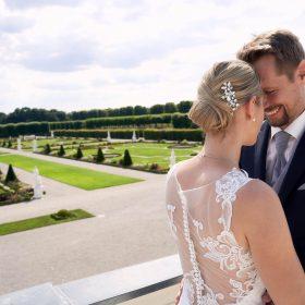 Brautpaar steht im Sommer im Barockgarten an Balustrade und strahlt sich an - Herrenhäuser Gärten Hannover © Hochzeitsfotograf www.hochzeitsverliebt.de