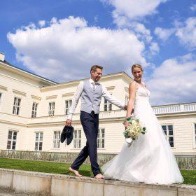 Brautpaar barfuß am Schloss Herrenhausen bei blauem Himmel, Schönwetterwolken und Sonnenschein - Herrenhäuser Gärten Hannover © Hochzeitsfotograf www.hochzeitsverliebt.de