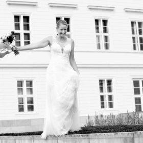 Lachende Braut mit figurbetontem Spitzenkleid geht barfuß lachend auf Granitsteinen und hält Schuhe und Brautstrauß am ausgestreckten Arm - Herrenhäuser Gärten Hannover © Hochzeitsfotograf www.hochzeitsverliebt.de