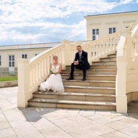 Das Brautpaar sitzt bei Sonnenschein und Schleierwolken mit blauem Himmel auf der hellen und geschwungenen Steintreppe - Herrenhäuser Gärten Hannover © Hochzeitsfotograf www.hochzeitsverliebt.de