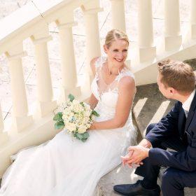 Braut und Bräutigam aus der Vogelperspektive sitzend auf der geschwungenen Steintreppe - Herrenhäuser Gärten Hannover © Hochzeitsfotograf www.hochzeitsverliebt.de