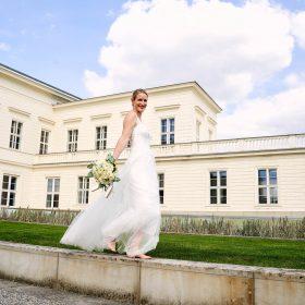 Braut mit figurbetontem Brautkleid in creme geht barfuß glücklich lachend in die Kamera schauend auf Steinen entlang - Herrenhäuser Gärten Hannover © Hochzeitsfotograf www.hochzeitsverliebt.de