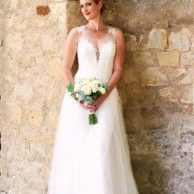 Die Braut im cremefarbenen Spitzenkleid steht in der hellen Steinnische und lächelt in die Kamera - Herrenhäuser Gärten Hannover © Hochzeitsfotograf www.hochzeitsverliebt.de