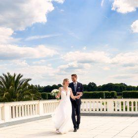 Tanzendes Brautpaar im Sommer auf der weissen Schlossterrasse mit blauem Himmel und Schönwetterwolken - Herrenhäuser Gärten Hannover © Hochzeitsfotograf www.hochzeitsverliebt.de