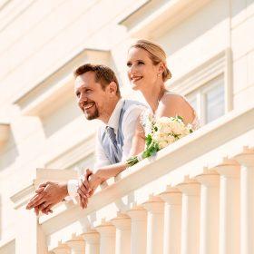 Strahlendes Brautpaar steht am Balkon vom Schloss bei vollem Sonnenschein - Herrenhäuser Gärten Hannover © Hochzeitsfotograf www.hochzeitsverliebt.de