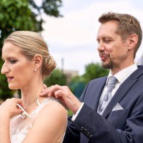 Bräutigam mit blauem Anzug rückt die Kette seiner Braut zurecht - Herrenhäuser Gärten Hannover © Hochzeitsfotograf www.hochzeitsverliebt.de