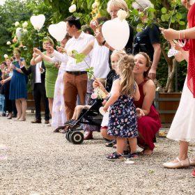 Hochzeitsgäste stehen im Garten Spalier und halten weisse Herzluftballons in den Händen - Herrenhäuser Gärten Hannover © Hochzeitsfotograf www.hochzeitsverliebt.de