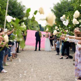 Cremefarbene Rosen werden von Gästen gehalten, während das Brautpaar am Ende vor einem pinken Tuch stehen bleibt - Herrenhäuser Gärten Hannover © Hochzeitsfotograf www.hochzeitsverliebt.de