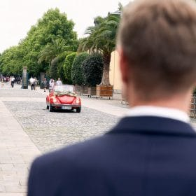 Roter VW Käfer fährt auf wartenden Bräutigam in Allee zu - Herrenhäuser Gärten Hannover © Hochzeitsfotograf www.hochzeitsverliebt.de