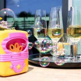Sektempfang im Freien mit Seifenblasen und gefüllten Sektgläsern in der Sonne am Tisch - Schlossküche Herrenhäuser Gärten Hannover © Hochzeitsfotograf www.hochzeitsverliebt.de
