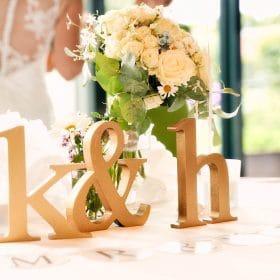 Initialen auf weisser Tischdecke mit Brautstrauß und Braut in Unschärfe - Schlossküche Herrenhäuser Gärten Hannover © Hochzeitsfotograf www.hochzeitsverliebt.de