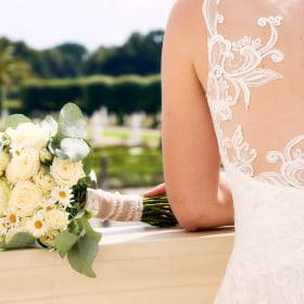 Rückenansicht der Braut mit Spitzenkleid und liegendem Brautstrauß aus Champagnerrosen auf Balustrade - Herrenhäuser Gärten Hannover © Hochzeitsfotograf www.hochzeitsverliebt.de