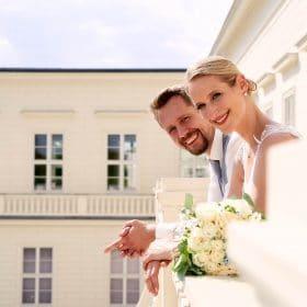 Hochzeitspaar steht im Sommer am Schlossbalkon und lächelt seitlich schauend in die Kamera - Herrenhäuser Gärten Hannover © Hochzeitsfotograf www.hochzeitsverliebt.de