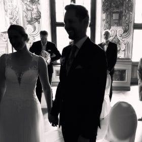 Brautpaar steht Händchen haltend mit ebenfalls stehenden Gästen im Hintergrund des Trauzimmers - Frühlingszimmer Herrenhäuser Gärten Hannover © Hochzeitsfotograf www.hochzeitsverliebt.de