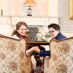 Brautpaar sitzt Hände haltend in opulenten Sesseln und dreht sich lächelnd zur Kamera um - Schloss Richmond Braunschweig © Hochzeitsfotograf www.hochzeitsverliebt.de