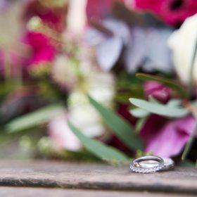 Brautstrauß in Rosatönen auf der Holzbank mit silbernen Ringen im Vordergrund - Französischer Garten Celle © Hochzeitsfotograf www.hochzeitsverliebt.de