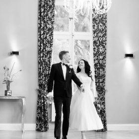 Schwarzweissfoto vom Hochzeitspaar, das durch den Raum mit Kronleuchtern geht - Schlösschen Bad Nenndorf © Hochzeitsfotograf www.hochzeitsverliebt.de