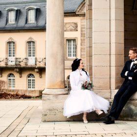 Braut und Bräutigam sitzen auf Gebäudeabsatz mit hellen Säulen - Kurpark Bad Nenndorf © Hochzeitsfotograf www.hochzeitsverliebt.de