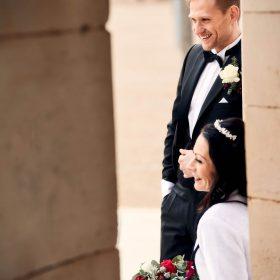 Durch eine Steinlücke fotografiertes, herzlich lachendes Brautpaar - Kurpark Bad Nenndorf © Hochzeitsfotograf www.hochzeitsverliebt.de