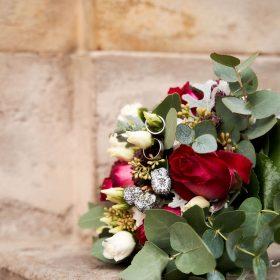 Rotgrüner Brautstrauß mit silbernen Eheringen auf sandfarbener Steinmauer - Kurpark Bad Nenndorf © Hochzeitsfotograf www.hochzeitsverliebt.de