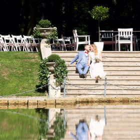 Das Brautpaar sitzt in der Sonne auf den Stufen nah beisammen und spiegelt sich im Wasser- Schloss Eldingen © Hochzeitsfotograf www.hochzeitsverliebt.de