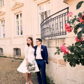 Brautpaar steht an der hellen Schlossfassade mit pinken Rosen Gartenrosen im Vordergrund - Schloss Richmond Braunschweig © Hochzeitsfotograf www.hochzeitsverliebt.de