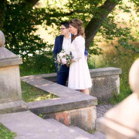 Das Brautpaar steht an der Treppe im Grünen mit charakteristischen Säulen - Schloss Richmond Braunschweig © Hochzeitsfotograf www.hochzeitsverliebt.de