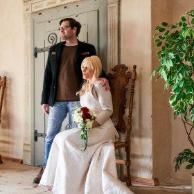 Stehender Bräutigam hält seine Hand auf der Schulter seiner sitzenden Braut im hellen Raum mit Holzfußboden - Schloss Schöningen © Hochzeitsfotograf www.hochzeitsverliebt.de