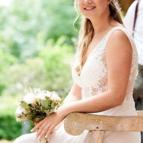 Die Braut sitzt auf der Holzbank mit Lehne und hält ihren Braustrauß in crem fest - Standesamt Winsen Aller © Hochzeitsfotograf www.hochzeitsverliebt.de
