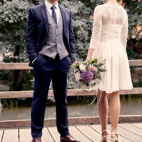 Braut in weiss und Bräutigam mit blauem Anzug stehen am Holzsteg und lehnen am Geländer - Junkerhof Wittingen © Hochzeitsfotograf www.hochzeitsverliebt.de