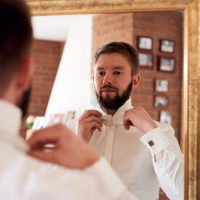 Bräutigam mit Bart bindet sich seine helle Fliege und sieht und den Spiegel - Hof Wietfeldt Bennebostel © Hochzeitsfotograf www.hochzeitsverliebt.de