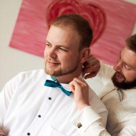 Bräutigam hilft seinem Freund beim binden der Türkisen Fliege im Raum mit rosa Wandbild - Hof Wietfeldt Bennebostel © Hochzeitsfotograf www.hochzeitsverliebt.de