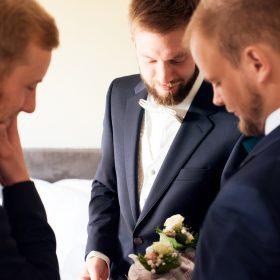Bräutigam in dunkelblauem Anzug steht mit zwei Freunden zusammen und schaut auf Anzugstecksträuße - Hof Wietfeldt Bennebostel © Hochzeitsfotograf www.hochzeitsverliebt.de