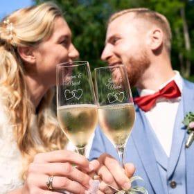 Zwei Champagnergläser mit Gravur werden vom Brautpaar in die Kamera gehalten -  Schloss Eldingen © Hochzeitsfotograf www.hochzeitsverliebt.de