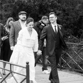 Schwarzweissfoto vom Brautpaar mit Freunden auf der Brücke - Schlosspark Celle © Hochzeitsfotograf www.hochzeitsverliebt.de