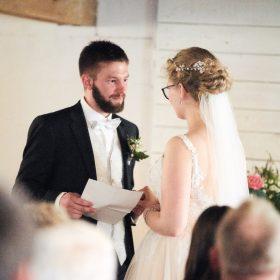 Stehendes Brautpaar in weiss und dunkelblau halten sich fest und geben sich ihr Eheversprechen- Hof Wietfeldt Bennebostel © Hochzeitsfotograf www.hochzeitsverliebt.de