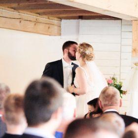 Brautpaar gibt sich stehend während der Trauung einen Kuss vor der Gesellschaft - Hof Wietfeldt Bennebostel © Hochzeitsfotograf www.hochzeitsverliebt.de