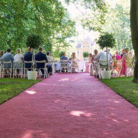 Hochzeitsgesellschaft bei Freitrauung mit weissen Stühlen und  rotem Teppich - Schloss Eldingen © Hochzeitsfotograf www.hochzeitsverliebt.de