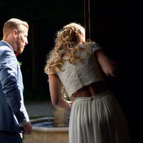 Brautpaar in weiss und hellblau schaut durch die Tür ins helle nach draussen - Schloss Eldingen © Hochzeitsfotograf www.hochzeitsverliebt.de