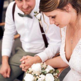 Das Brautpaar sitzt Hände haltend bei der Trauung - Standesamt Winsen Aller © Hochzeitsfotograf www.hochzeitsverliebt.de