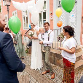 Weisse Tauben aus Luftballons und grüne Ballons werden von Gästen und dem Hochzeitspaar am Rathaus gehalten - Standesamt Winsen Aller © Hochzeitsfotograf www.hochzeitsverliebt.de