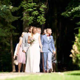 Brautpaar schreitet Hände haltend mit der Hochzeitsgesellschaft den Weg im Schlossgarten entlang - Schloss Eldingen © Hochzeitsfotograf www.hochzeitsverliebt.de