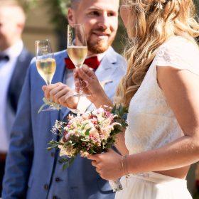 Das Hochzeitspaar stößt in der Sonne miteinander an - Schloss Eldingen © Hochzeitsfotograf www.hochzeitsverliebt.de