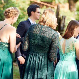 Rückenansicht der alle in Grüntönen gekleideten Frauen im Grünen - Hof Wietfeldt Bennebostel © Hochzeitsfotograf www.hochzeitsverliebt.de