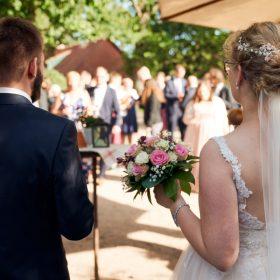 Brautpaar im Freien von hinten während der Ansprache zum Sektempfang mit der Gesellschaft im Hintergrund - Hof Wietfeldt Bennebostel © Hochzeitsfotograf www.hochzeitsverliebt.de